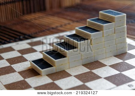 Piramid of domino pieces on the bamboo brown wooden table background
