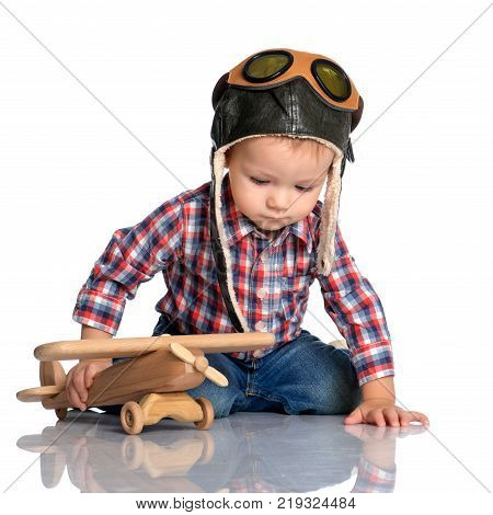 Boy in helmet pilot playing with a toy wooden airplane in the clouds, dreaming of becoming a pilot.Isolated on white background.