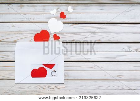 Wedding ring for St. Valentine's Day. The offer to get married. A gift for St. Valentine's Day. Envelope with a ring on a wooden background. Copy space. Marriage propose.