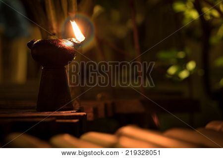 Classic kerosene oil lantern lamp burning with a soft glow light in an antique rustic country barn with aged wood floor