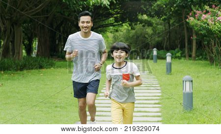 Asian father runing together with his little son in park in summer