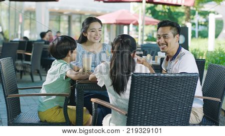 Chinese parents & kids taking break and enjoying drinks at outdoor cafe seat