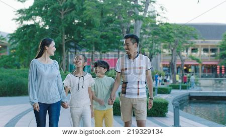 Asian family walking together on promenade excited when looking at each other