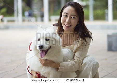 Asian beauty embracing her dog smiling at camera outdoor in garden