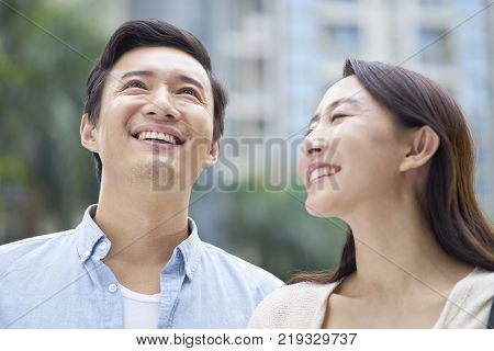 Asian couple laughing while enjoying time outdoors in garden