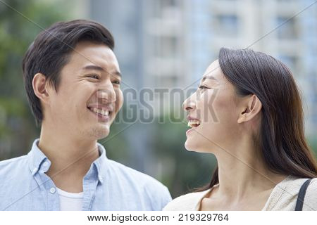 portrait of Asian couple laughing at each other while walking outdoor in garden