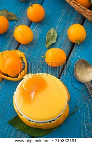 A sweet orange jelly with cumquats and tangerine lobes on blue rustic wooden background