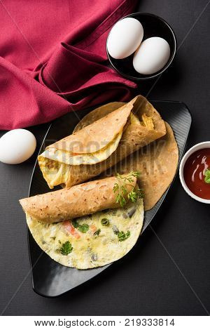 omelette / omelette chapati roll or Indian bread or roti rolled with omlet. Popular, quick and healthy recipe for kid's tiffin or lunch box