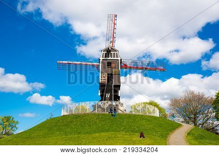 Bruges, Belgium - April 17, 2017: Windmill in Bruges, Northern Europe, Belgium. Historical building preserved for tourism in the city, along the canals.