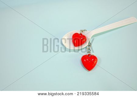 A pair of Red heart symbol with steel chain in a white spoon with light green paper background for valentine's day concept