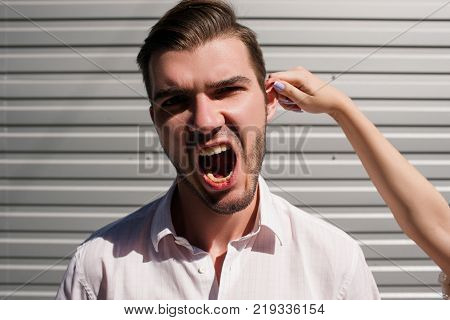 guilty guy gets comical punishment from his girlfriend. make-believe way to discipline your boyfriend. grabbing the ear. pain scream violence abuse concept