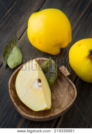 Quince or queen apple lobe in a craft wooden plate on black rustic wooden table