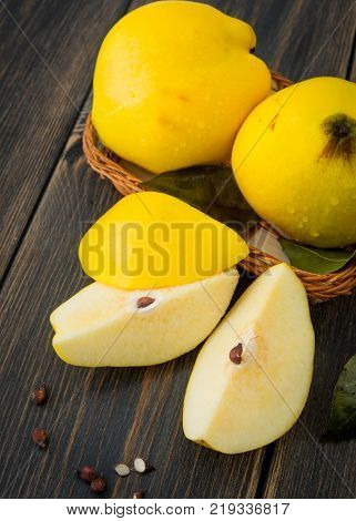 A wicker basket of yellow quince or queen apple autumn fruits, sliced lobules and seeds on black rustic wooden background close-up