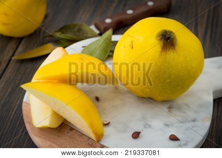 Sliced yellow quince or queen apple autumn fruits with seeds on marble cooking board close-up