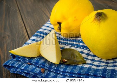 Sliced yellow quince or queen apple fruits with seeds on blue checkered towel close-up