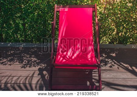 Relaxation Concept : Red wooden daybed setting on wooden floor beside swimming pool at the resort. (Selective focus)