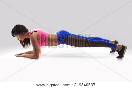 beautiful, slender athlete woman performs exercises in the studio