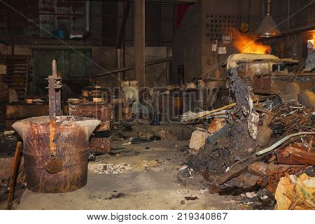 sparks fly as scrap steel melts down in an induction furnace at a small old chinese foundry
