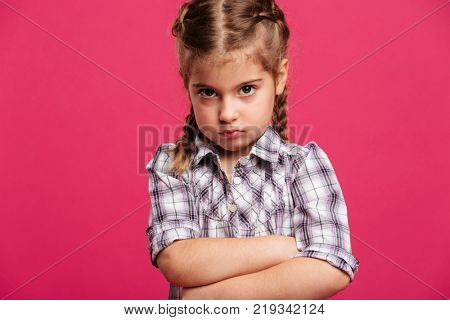 Photo of angry little girl child standing isolated over pink background. Looking camera.