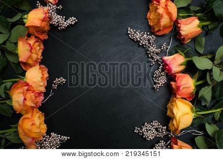 Orange and red autumn roses dark background with silver beads adornment. Symbol of deep feelings and elation. Copyspace concept