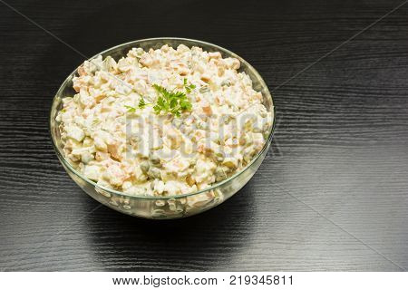 Dish for vegetarians. Bowl with vegetable salad prepared for the holiday on a wooden table.