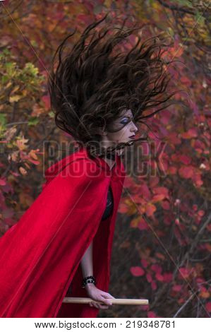 Young beautiful and mysterious Witch woman Flying on the Broom in Red autumn Forest, in black Dress and Red Cloak
