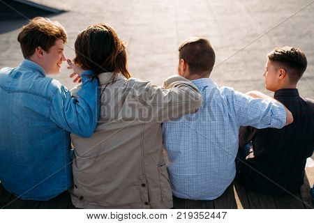 Men friendship. Back view of young teenagers hugging. Bff support unity teamwork concept
