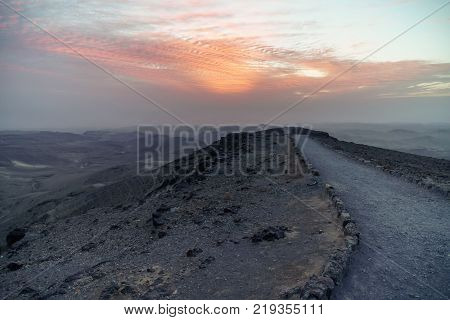 Magic sunrise dawn over holy land judean desert in Israel. Landscape with beautiful red sun and blue clouds. Road to infinite violet land. Nobody on photo.