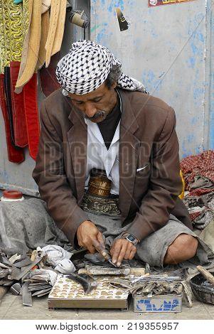SANAA, YEMEN - SEPTEMBER 18, 2006: Unidentified Yemeni man sharpens janbiya in Sanaa, Yemen. Janbiya is a traditional dagger and a mandatory attribute of Yemeni men's suit.