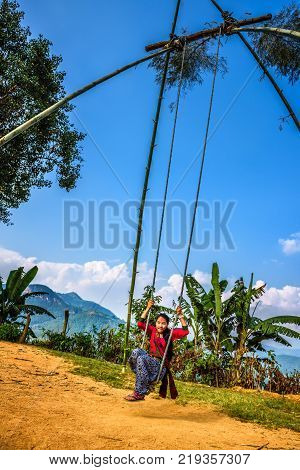 BANDIPUR, NEPAL - OCTOBER 22, 2015 : Nepalese girl playing on a traditional bamboo swing called linge ping.