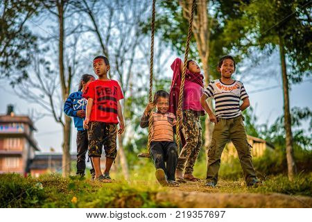 BANDIPUR, NEPAL - OCTOBER 22, 2015 : Nepalese children playing on a traditional bamboo swing called linge ping. Shallow DOF.