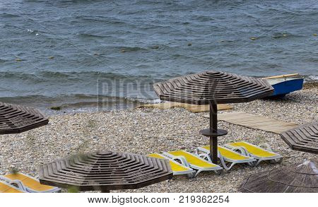 wooden sunshades and plastic sunbeds at a beach of black sea