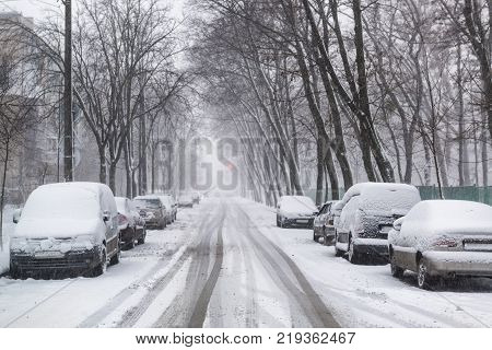 Heavy snowfall on the city streets in winter. Cars are covered by snow slippery road