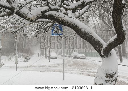 Heavy snowfall on the city roads in winter. Cars covered by snow