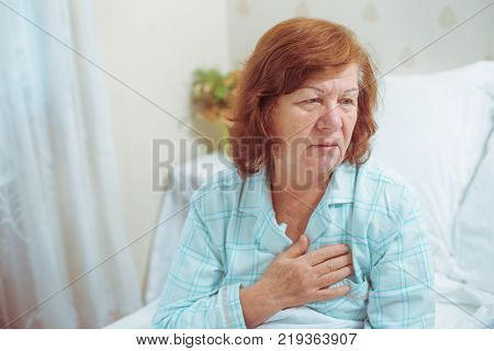Senior woman having heart attack at home, no one around. Red hair grandmother alone at her apartment got troubles with her health.
