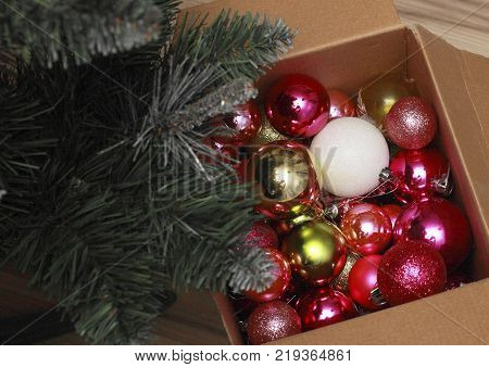 Near artificial Christmas trees is disclosed a box of bright shiny baubles - Christmas decorations. The branches of spruce covered with decorative frost looks like.