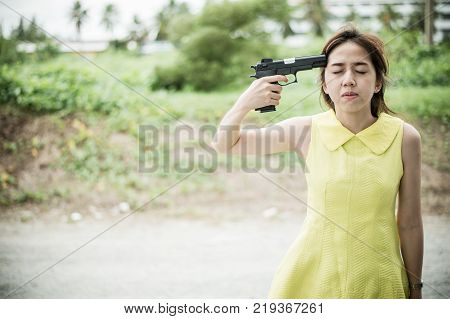 Stressed woman with holding gun on hand point to her head.She is saddened by the disappointment in love. concept of broken heart, heartbroken, lovelorn, Suicide. with copy space for text.