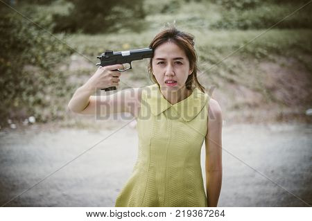 Stressed woman with holding gun on hand point to her head.She is saddened by the disappointment in love. concept of broken heart, heartbroken, lovelorn, Suicide.