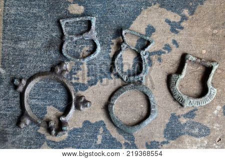 ILLUSTRATIVE EDITORIAL.Small bronze items 10-12 c.(found with metal detector near Kiev).Background - Russian school textbook Geography of Europe circa 1910. Kiev,Ukraine December 22 ,2017