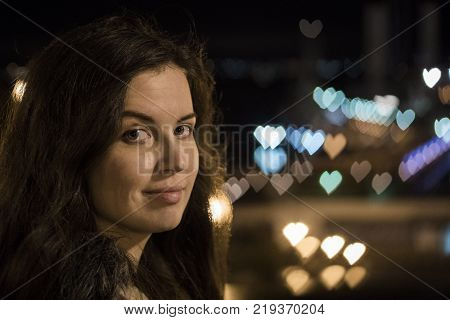 Young Brunette on the Street with bizarre bokeh shapes. Anamorphic lens type