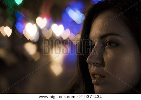 Young Brunette on the Street with bizarre bokeh shapes. Close-up portrait. Love and hearts. Anamorphic lens type