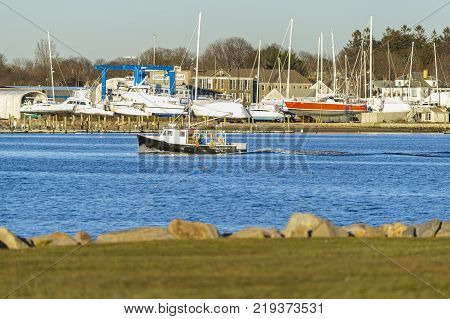 New Bedford Massachusetts USA - December 21 2017: Fishing boat Martha Elizabeth crossing New Bedford harbor with Fairhaven in background