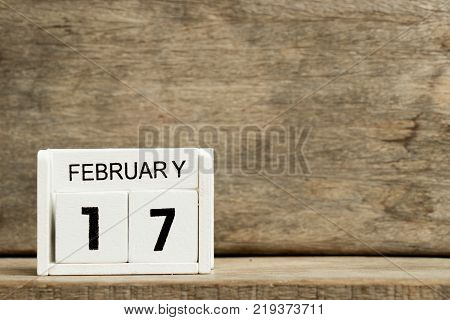 White block calendar present date 17 and month February on wood background