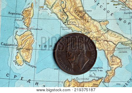 ILLUSTRATIVE EDITORIAL.Italian bronze coin 1862.Background - Russian school textbook Geography of Europe circa 1910. Kiev,Ukraine December 22 ,2017