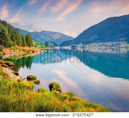 Colorful summer sunrise on Resia (Reschensee) lake. Resia village in the morning mist Province of Bolzano - South Tyro Italy Europe. Artistic style post processed photo.