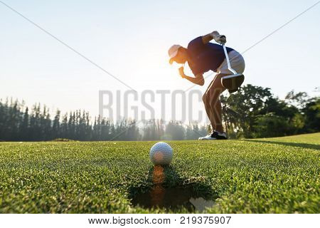 Golfer action to win after long putting golf ball on the green golf. morning time.
