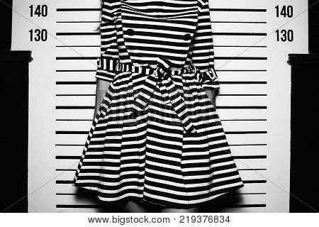 young woman in dress with line standing like for police photo