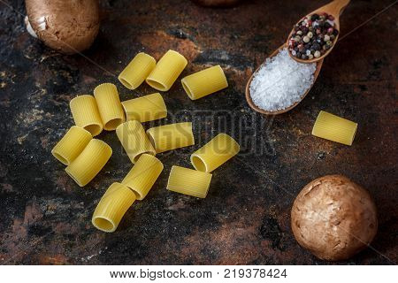 Coarse sea salt and pepper corns on black background with pasta