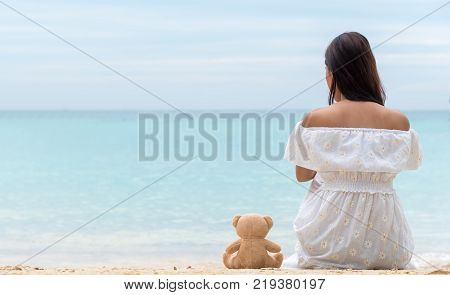 Single women in white dress sitting alone with teddy bear is a friend by the sea the girl who break heart is lonely