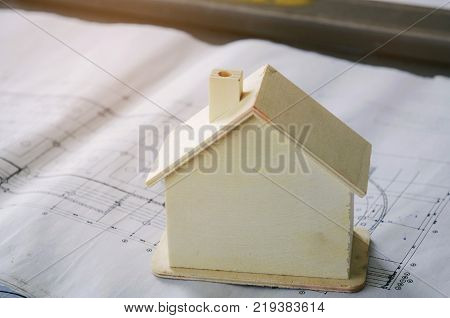 close up image of wooden house model on blueprint for plan start up project in construction site successful business industry architecture construction and housing project concept